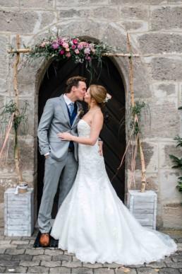 Brautpaarshooting Traubogen Küssen