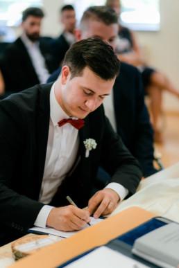 Bräutigam unterschreibt nach dem Ja Wort im Standesamt Bamberg, festgehalten von Julia Reif Fotografie